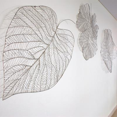 Wire leaf structures line the hallway outside the rooms